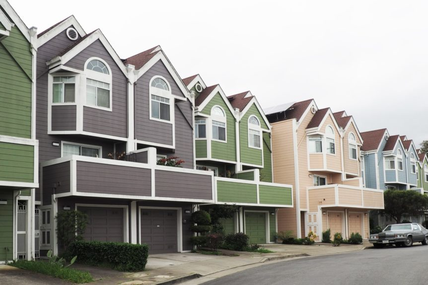 Townhouses in a row, one grey, one green and one beige. Relating to comparing fixed vs variable rate mortgages.