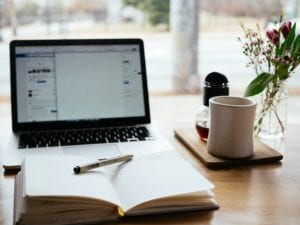 a wooden desk with flowers, a mug, a laptop, and a notebook open for taking notes on self-employed mortgages