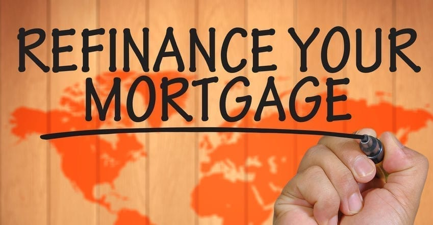Hand writing on clear surface in black marker 'refinance your mortgage' with a map outline in the background