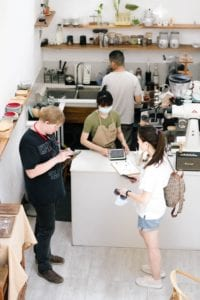 Four young adult employees in their coffeeshop workplace; highlighting how banks view employee income