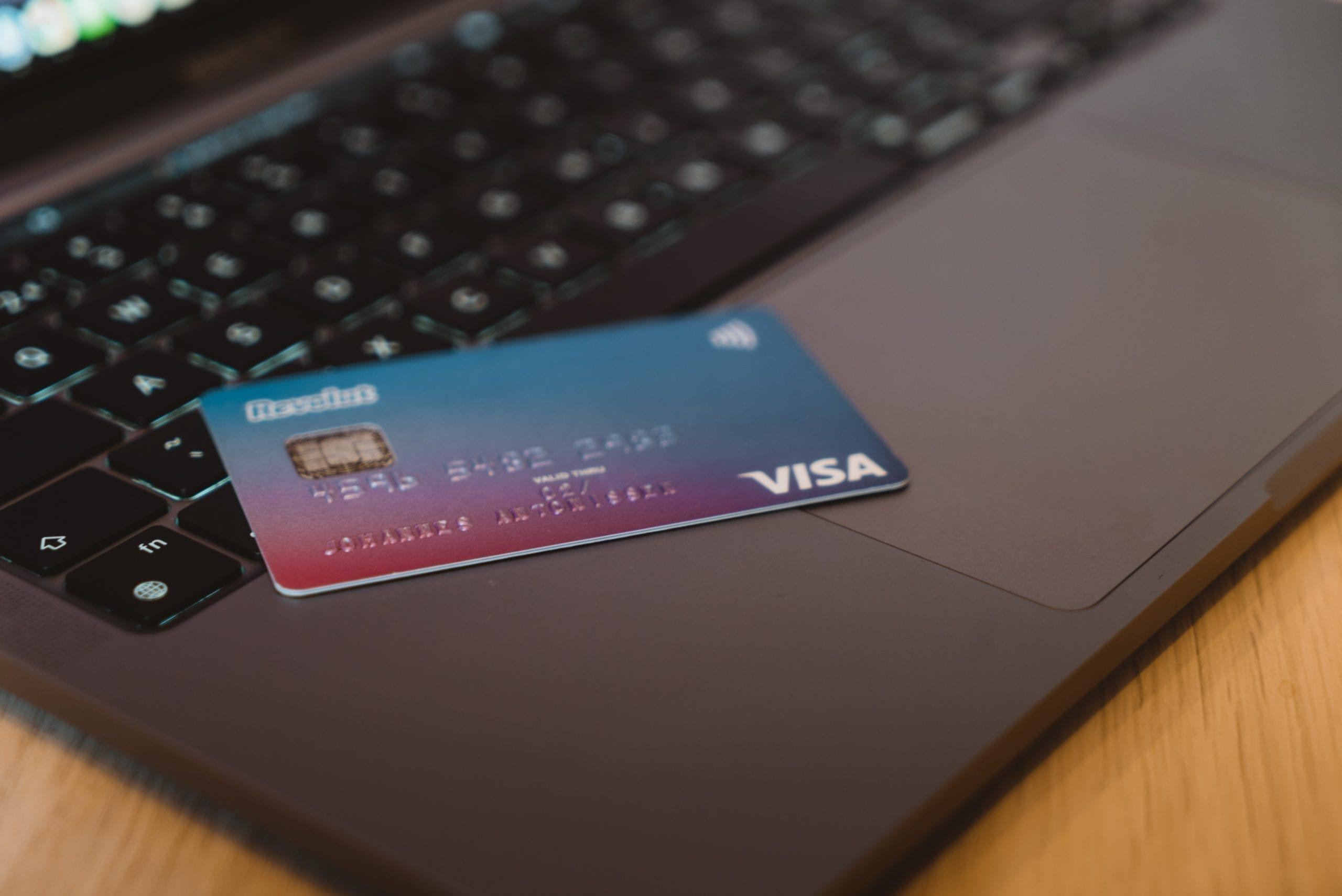 Closeup of visa credit card on laptop, in relation to acquiring credit