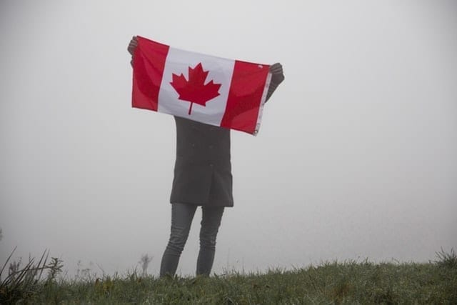 A woman holding up a Canadian flag outdoors on a foggy day; highlighting the New to Canada Mortgage program