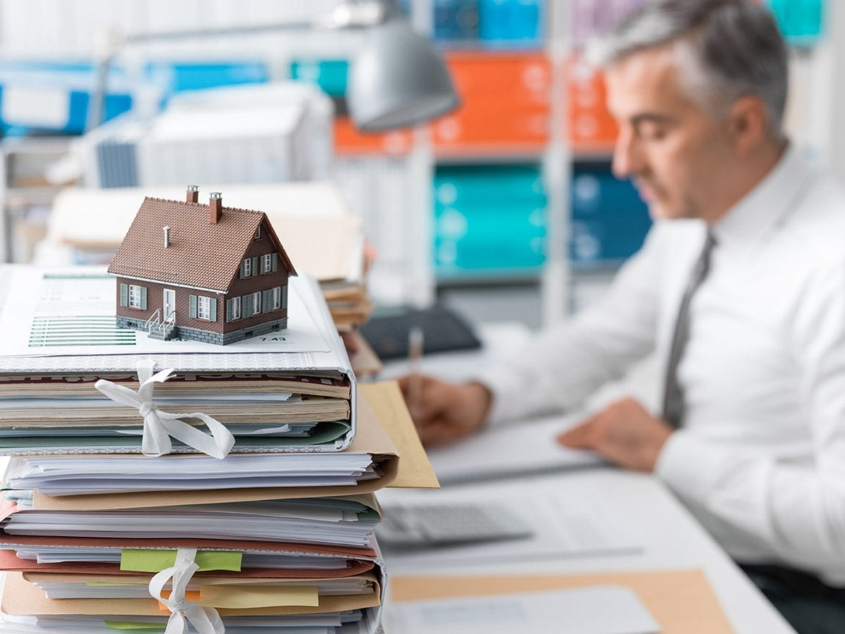Man sitting at desk with a pile of folders and a miniature house on top; highlighting the Kelowna mortgage blog