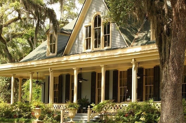 Two story family home among trees, closeup of front porch area; highlighting renewing your mortgage