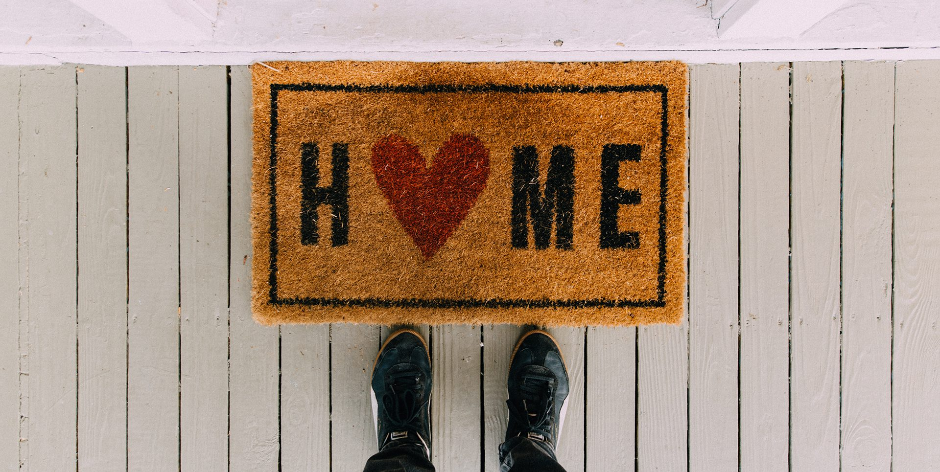 Welcome mat with the word 'home' and a heat, highlighting the mortgage process of buying and selling simultaneously