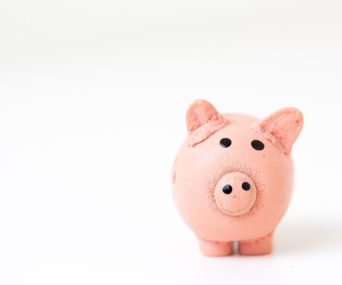 Pink handmade piggy bank on white surface and background; highlighting the financial considerations in buying and selling simultaneously