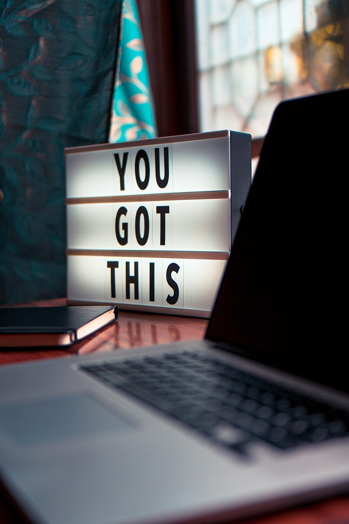 home office during the COVID-19 outbreak with a lighted sign on the desk with the words 'you got this'