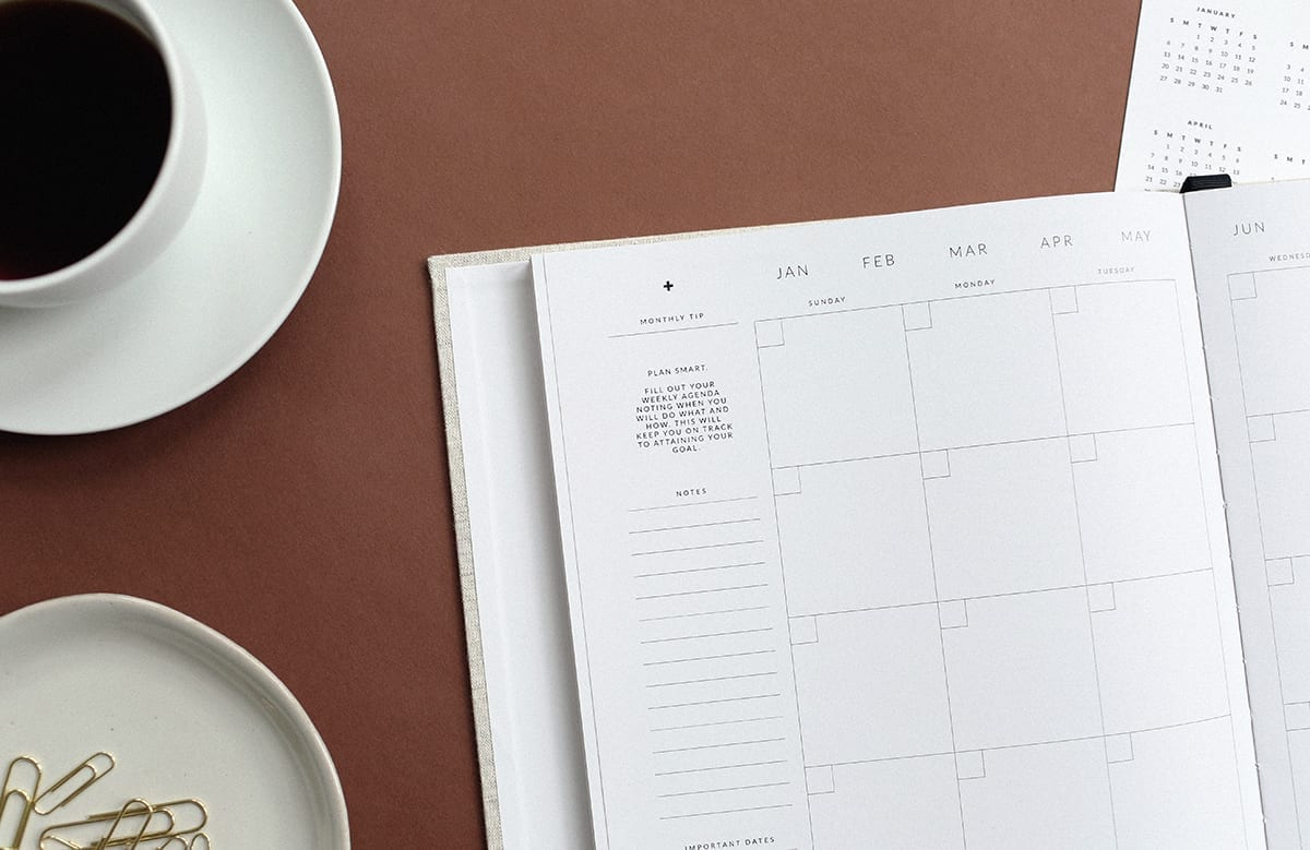 a calendar on a table with a cup of coffee, highlighting that planning is important for mortgage renewals and finding the best rate