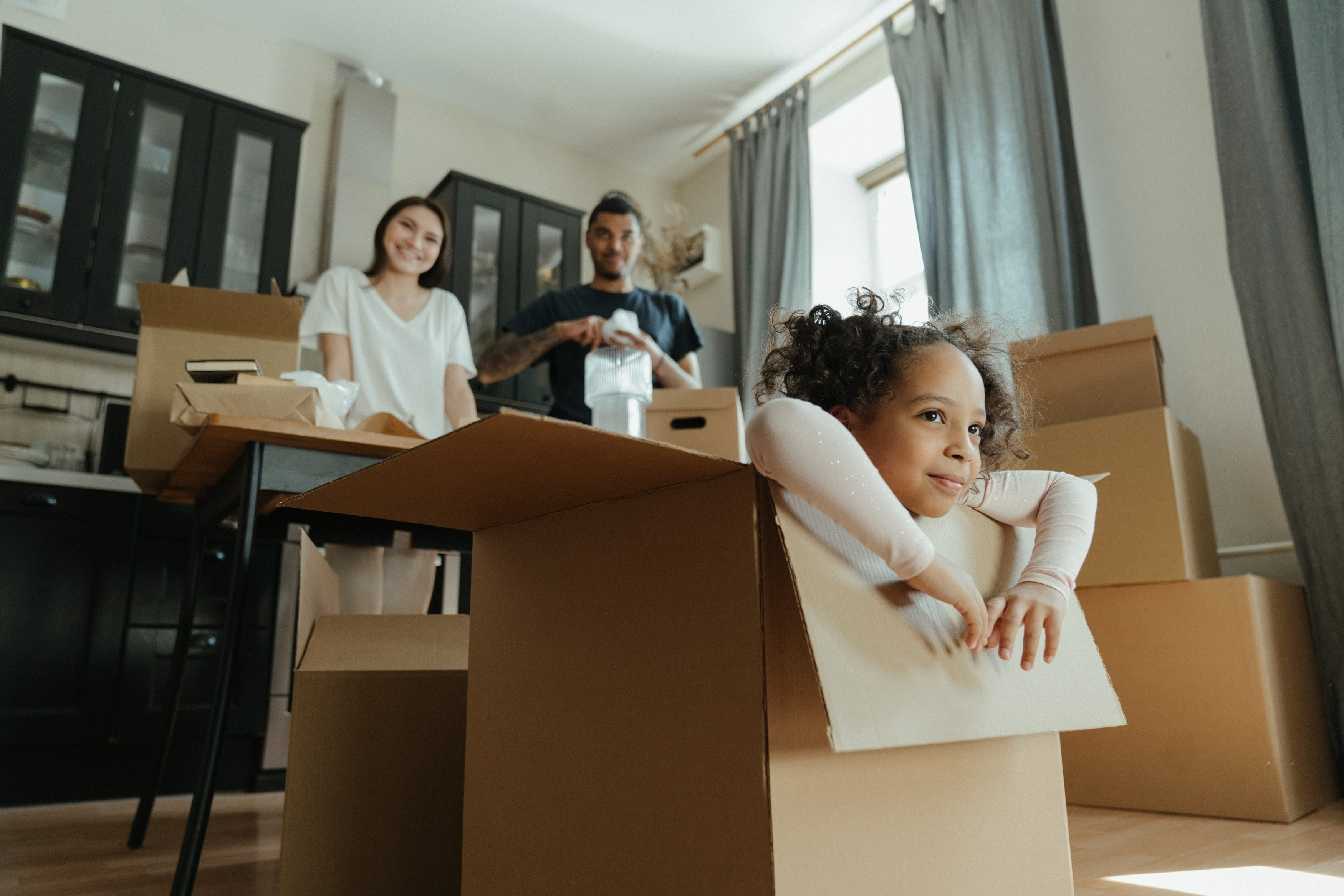 young girl playing in a moving box while parents watch, after choosing the right mortgage broker in their home buying process