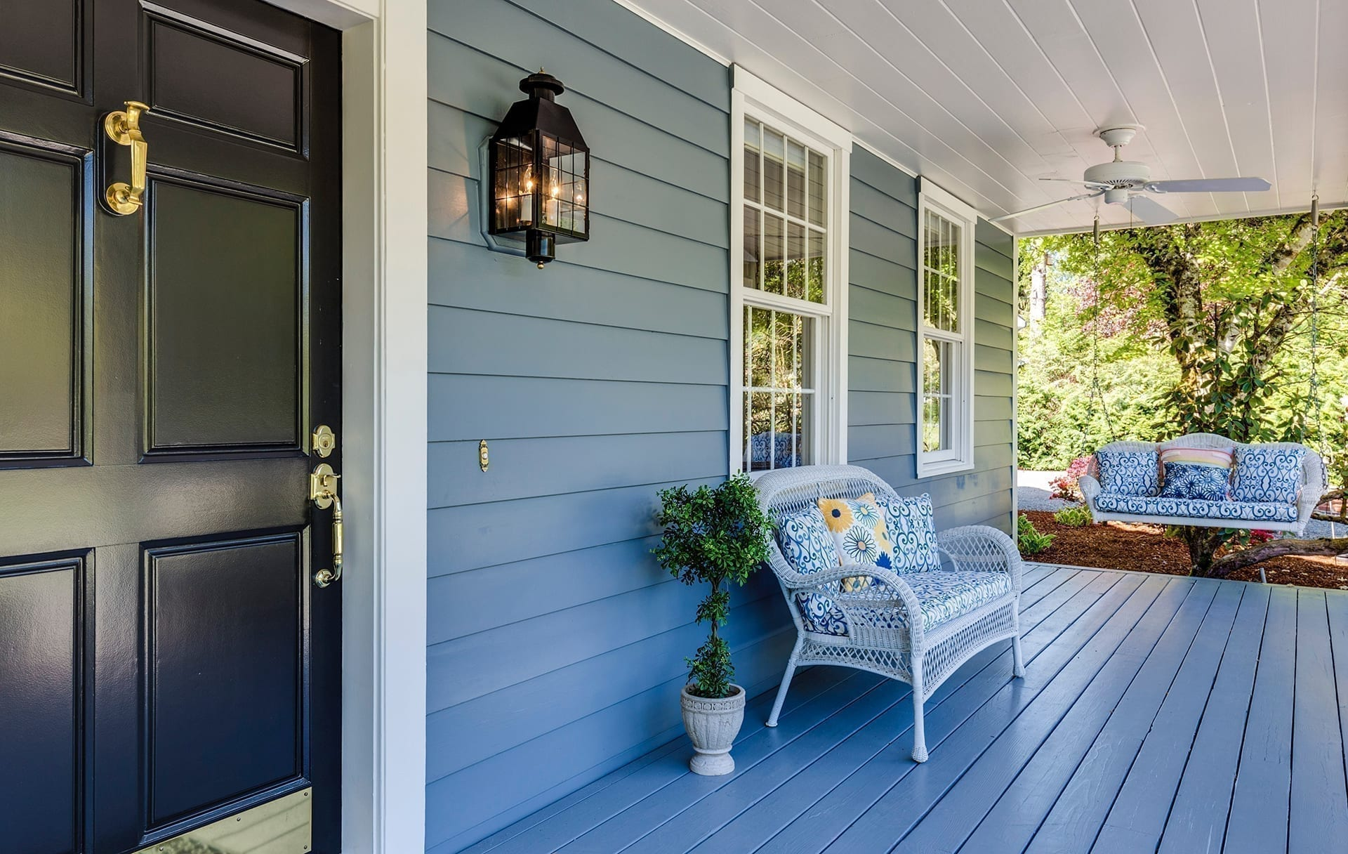 Front porch in blue with a dark door and outdoor furniture; highlighting the time to stat planning a mortgage