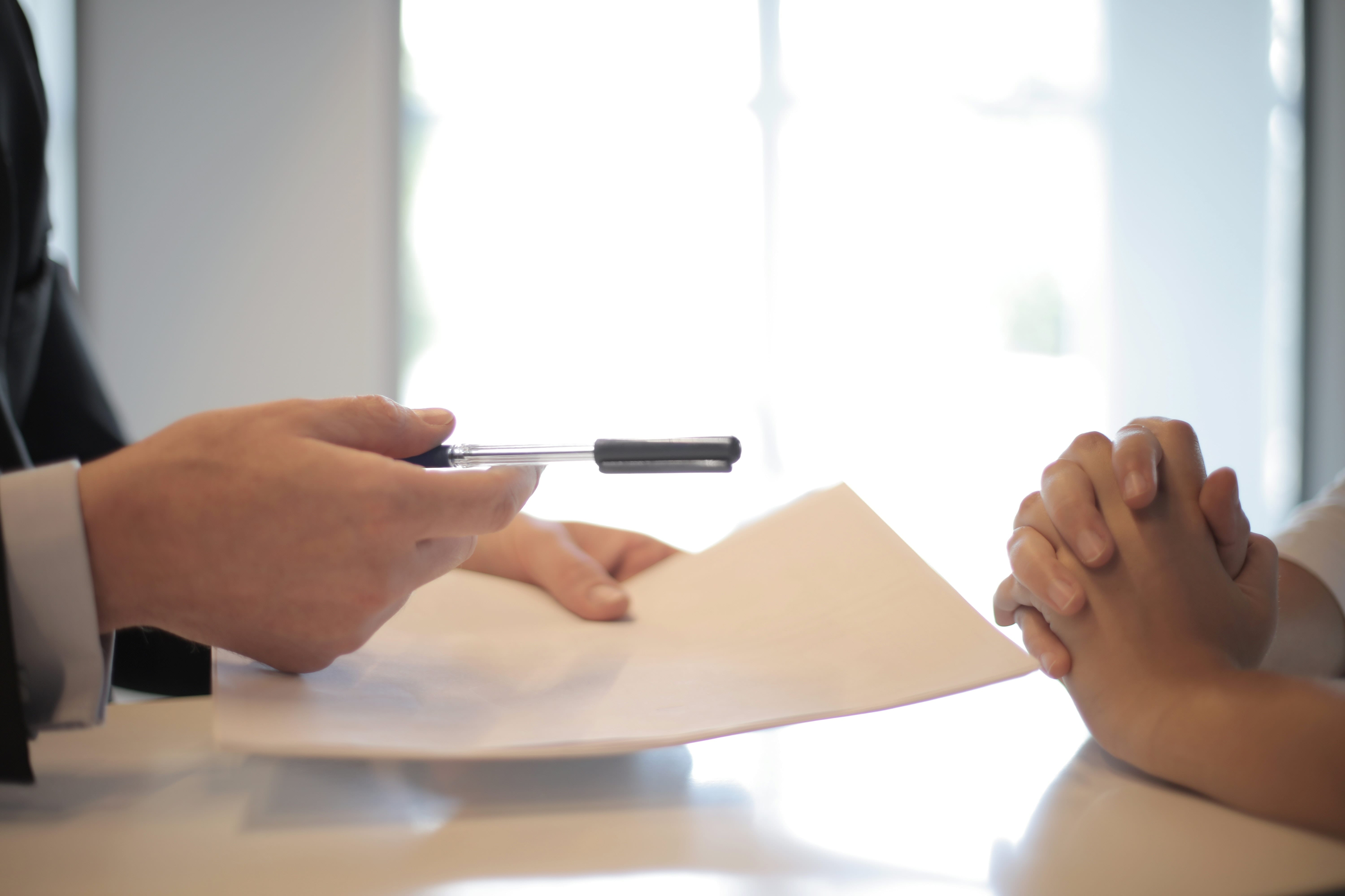 closeup of hand holding a pen and paper, in a gesture to hand this off to another person; highlighting securing a mortgage post covid 19