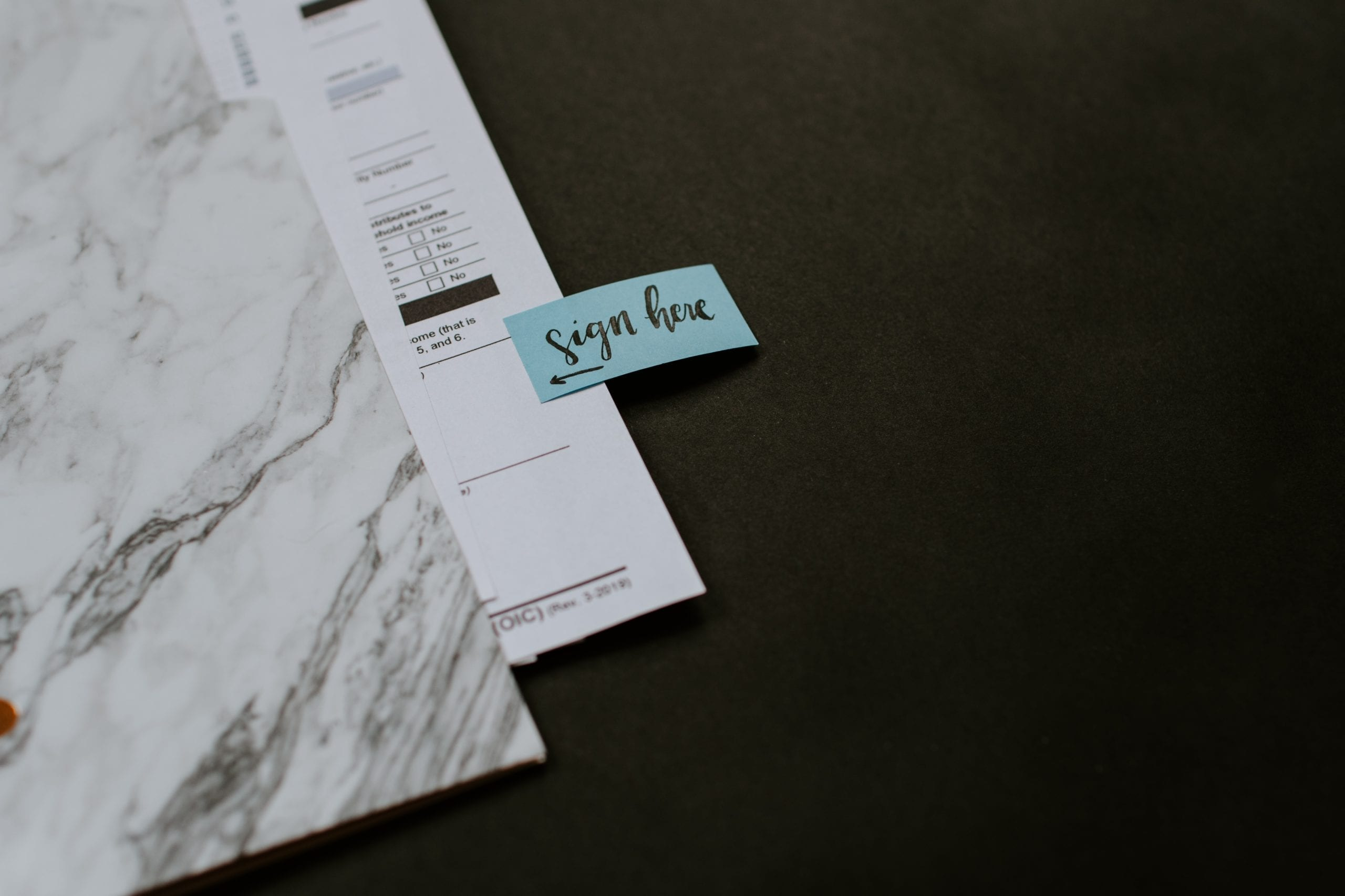 closeup of documents on a granite counter with a signature field and post it note saying sign here; highlighting refinance decisions