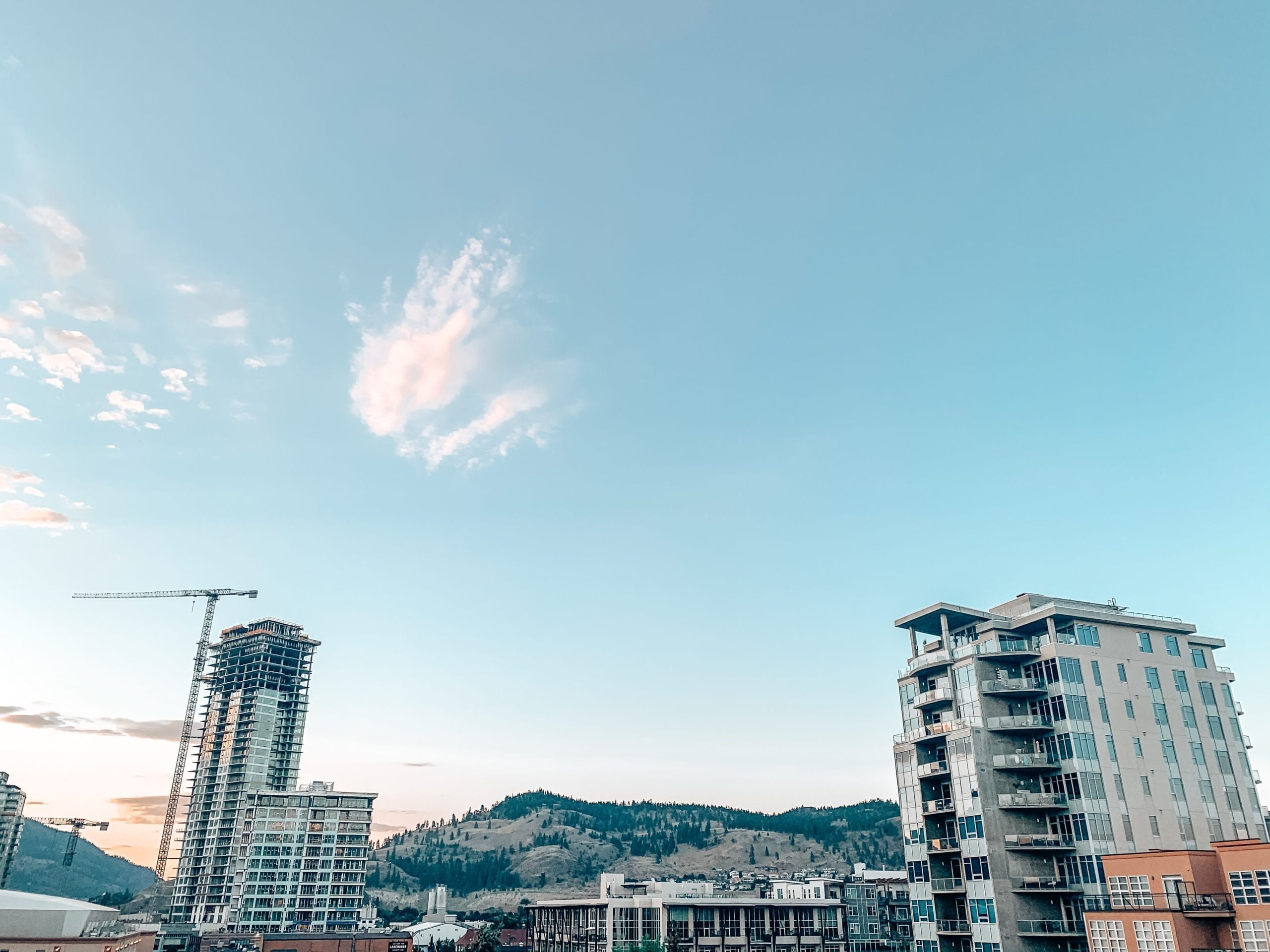downtown kelowna view of new condo construction, in reference to buying a second home but keeping the first