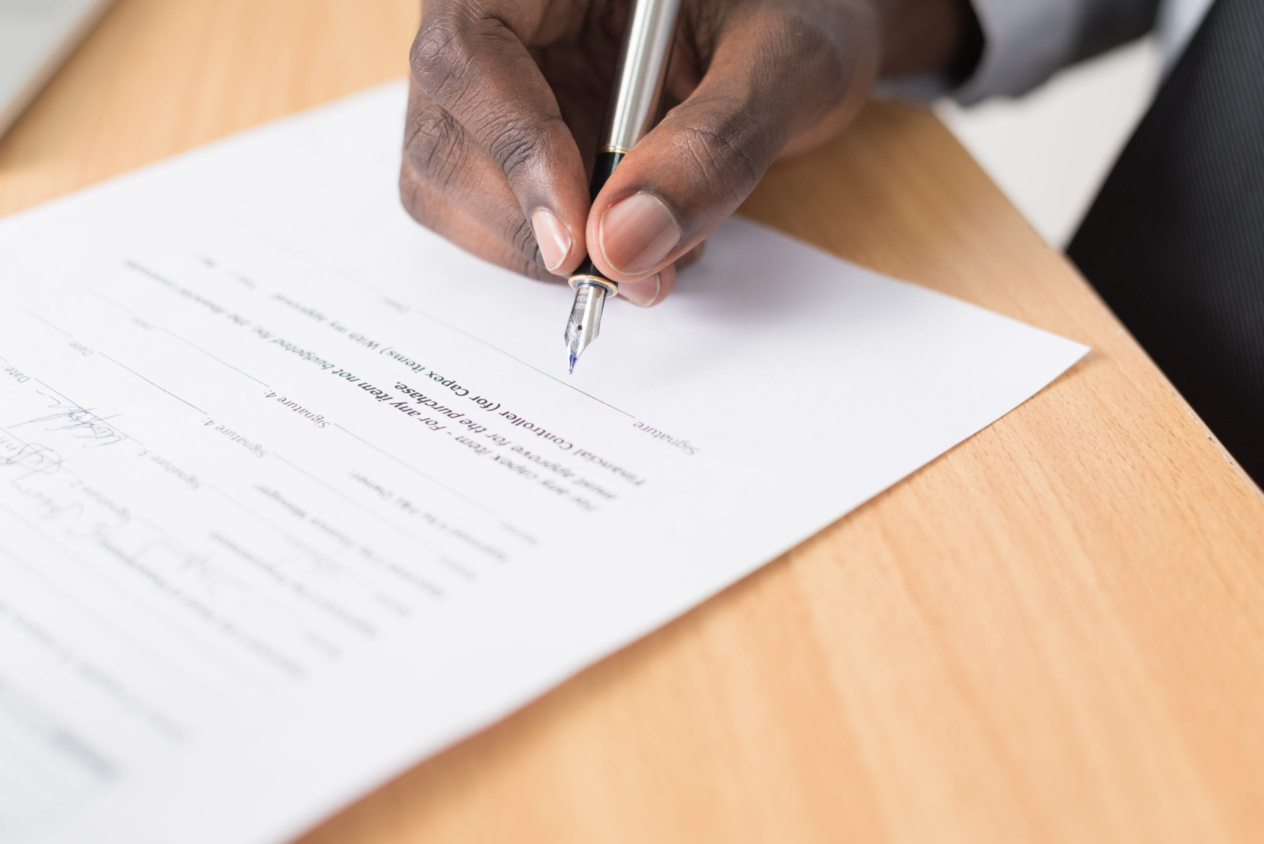 hand holding a pen and cosigning a mortgage document