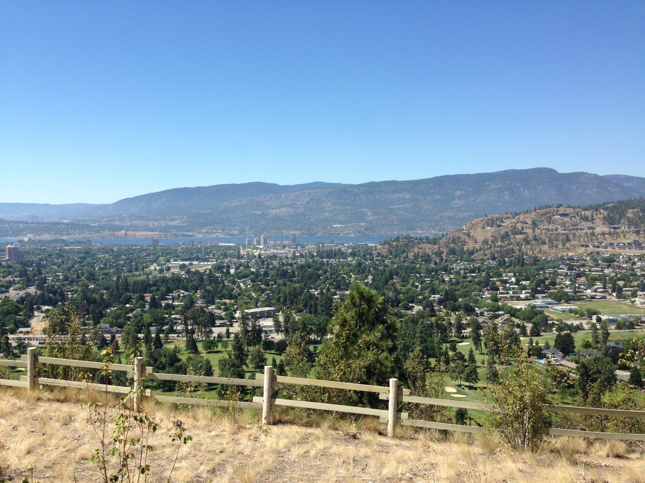 Valley view of residential Kelowna on a clear sunny day, with mountains and Okanagan lake in background