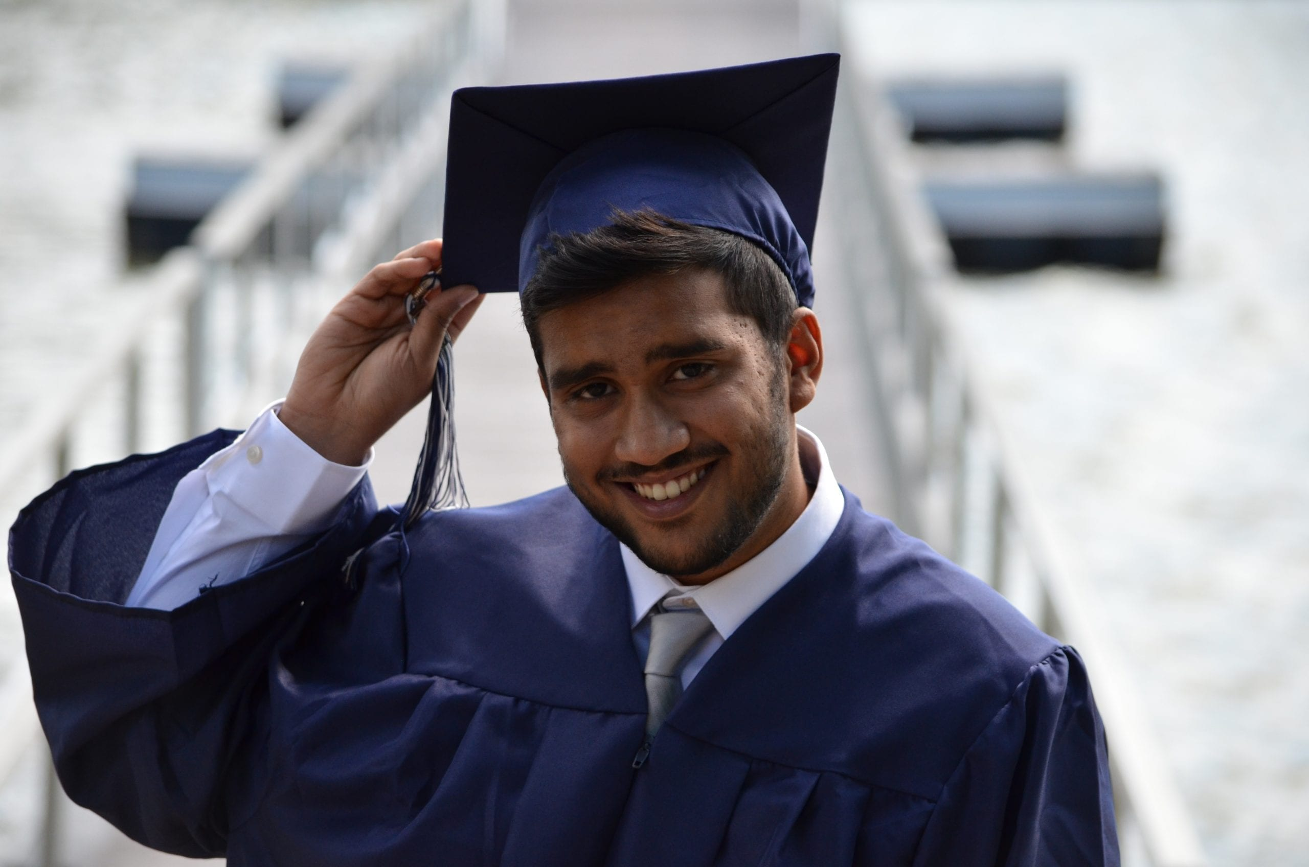 A recent college graduate in cap and gown, highlighting buying a house and qualifying for a mortgage with a student loan