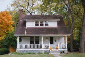 Modest, white Colonial style house with pumpkins lining the front step; relating to private lending mortgages.