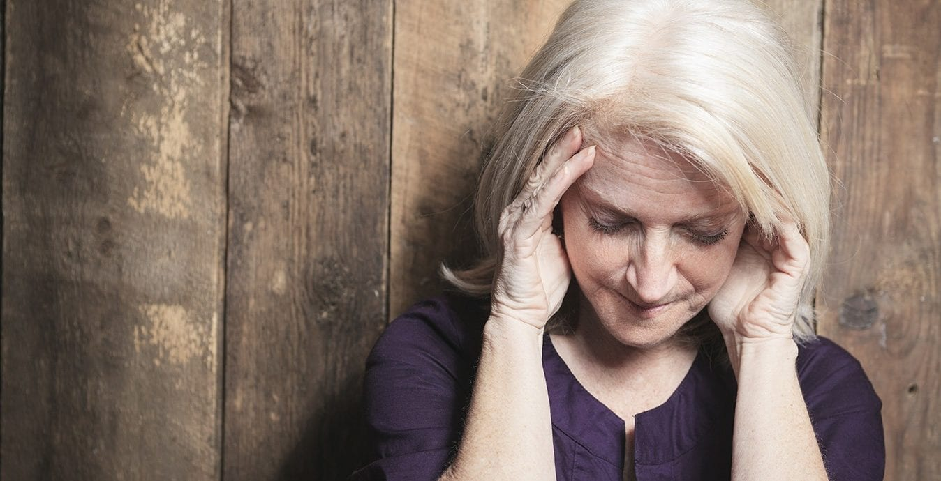 A depress senior woman with wood background; highlighting depression as a symptom of menopause