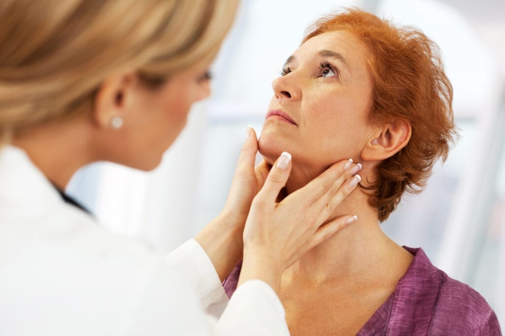 Close-up of a female doctor doing a medical examination. The focus is on the mature adult woman being examined in a thyroid exam