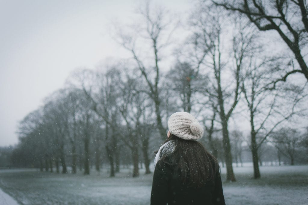 woman walking in light snow with trees in the background on a grey day; highlighting Seasonal Affective Disorder