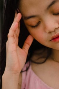 Woman holding head with headache, an area of treatment for neurokinetic therapy
