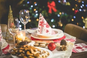 Closeup of christmas dinner table with cookies and a wine glass and party hat for surviving the holidays