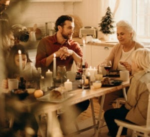 Family at table for Christmas Dinner during holidays with grandma and son and grandkids