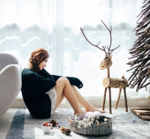 Woman sitting next to couch around christmas decor pondering surviving the holidays