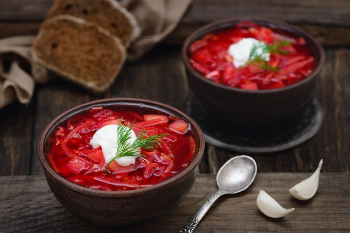 Vegetarian red beet borscht soup in bowls on an old wooden background