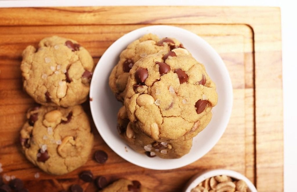 Vegan quinoa chocolate chip cookies on a wooden cutting board with a small white bowl holding a few cookies
