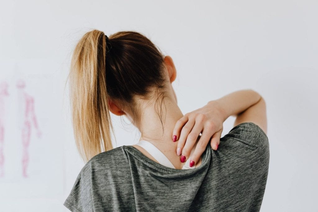 Woman pressing on a trigger point on her back, highlighting massage therapy as a treatment for headache relief.