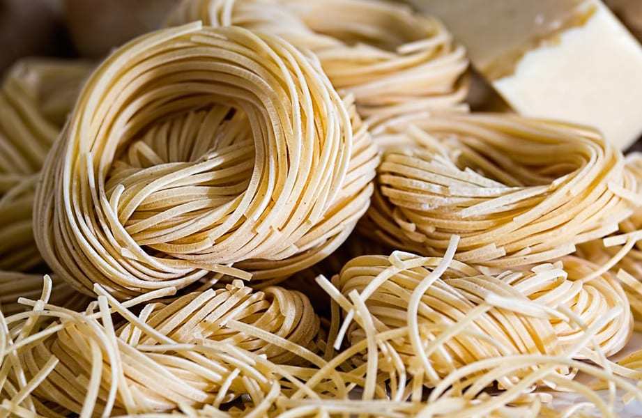 dried capellini pasta bundles with a block of parmesan and shallots