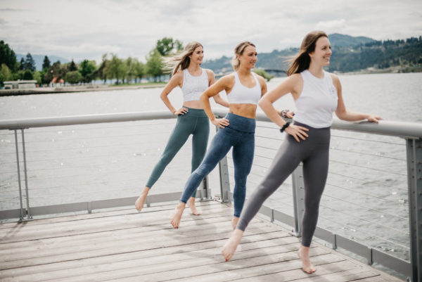 Three women in activewear on a boardwalk practising barre representing Barreroom onDEMAND's Spring Break Challenge.