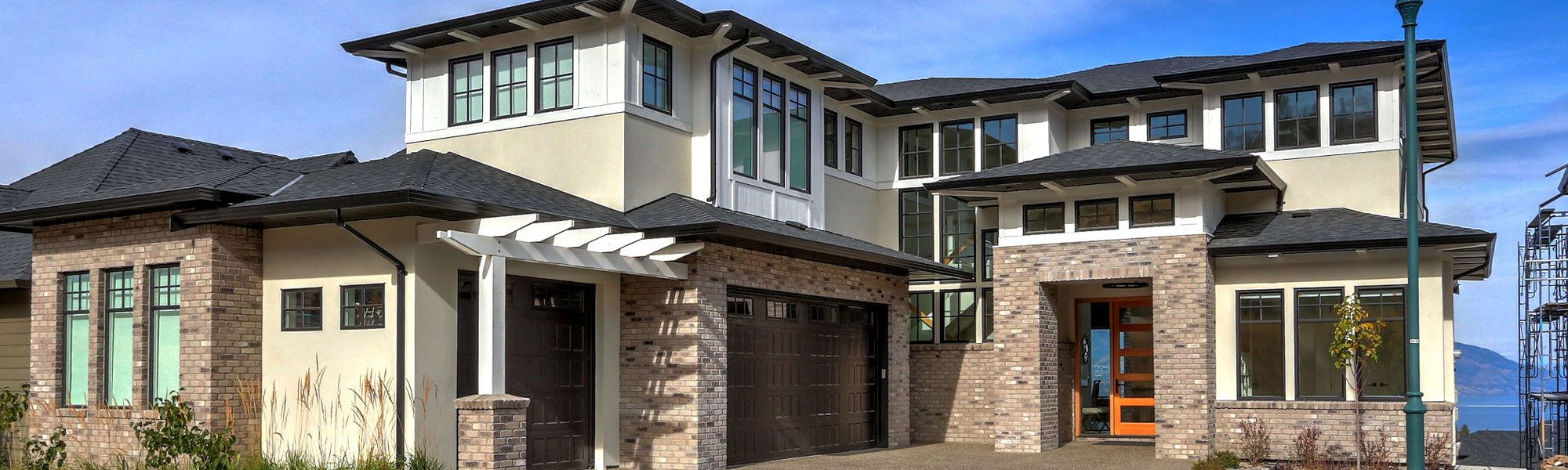 Closeup of 470 Rockview Lane front exterior with brick and white arbour over double garage