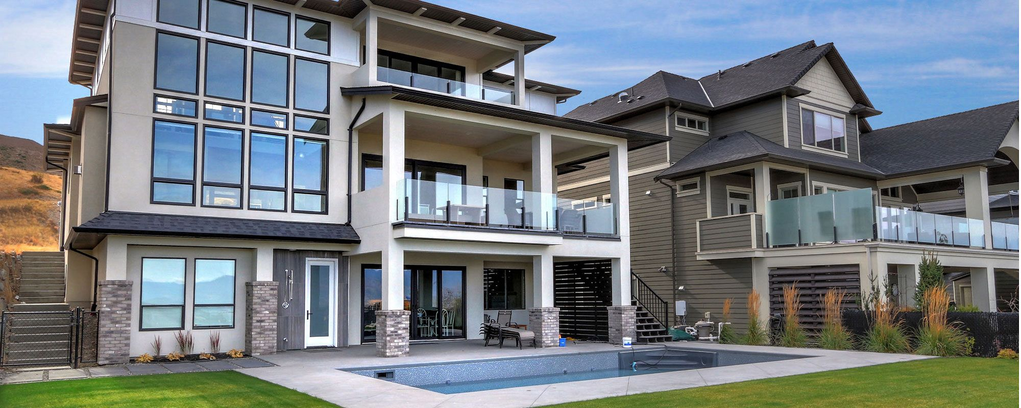 Back exterior of 470 Rockview Lane, with three floors, two decks and a patio with a large in-ground pool custom built by Stark Homes
