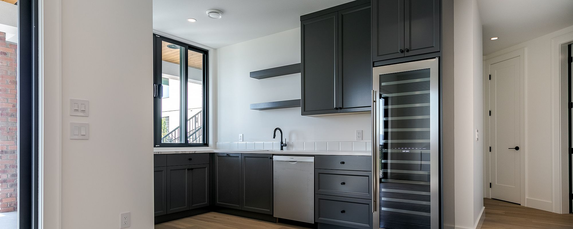 Custom basement wet bar with wine fridge and black cabinets by Stark Homes