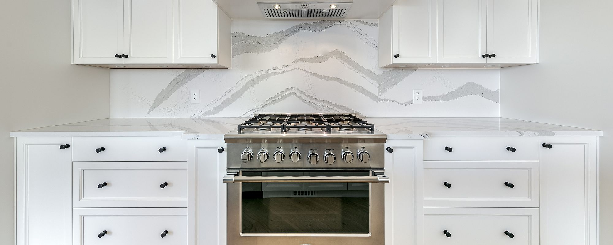 Closeup of a Stark Homes kitchen stove area with marble style backsplash and crisp white cabinets