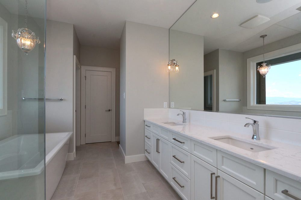 Bright white and spacious custom bathroom by Stark Homes at 462 Rockview Lane with twin sinks, a soaker tub, and a standing shower