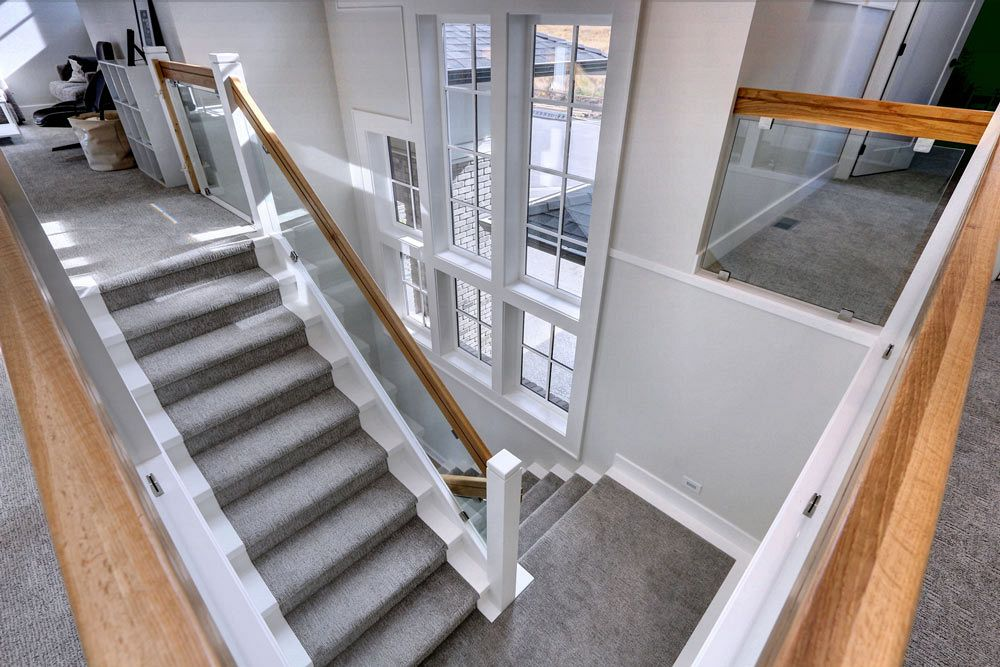 Custom home build view down from platform in open concept home, overlooking wooden railing and carpeted stairs with large windows
