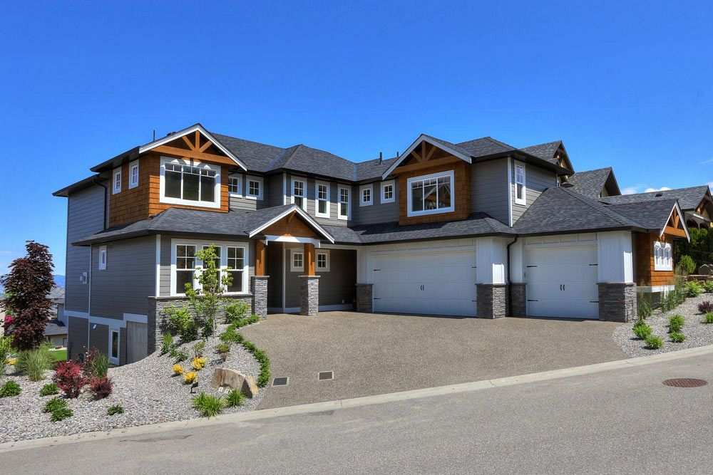 Road view of 462 Rockview Lane custom home build with white garages and stonework with wooden accents