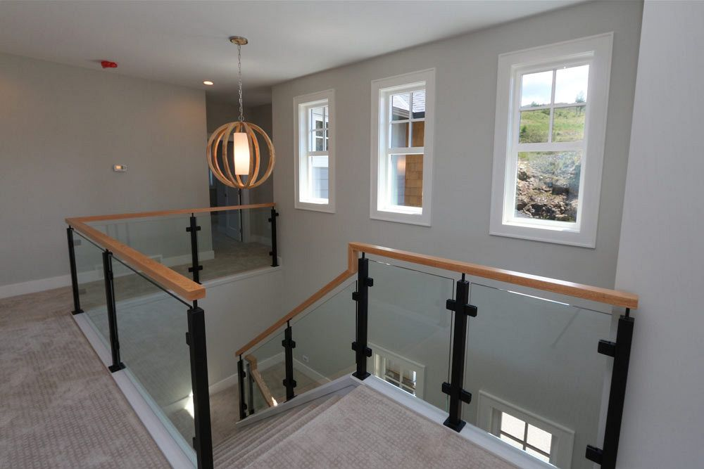 Open concept stairs and hallway with circular wooden light fixture