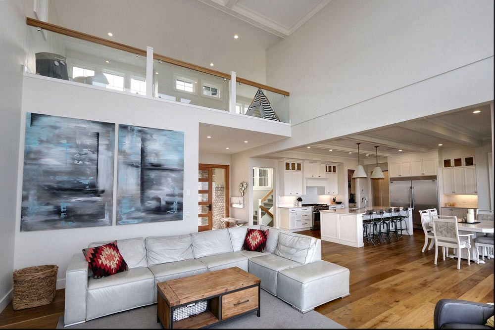 Interior design by Stark Homes for 470 Rockview Lane, featuring high ceilings and white bright furniture in an open concept living room and kitchen design