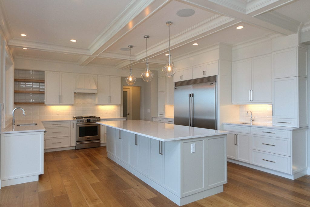 Custom built kitchen by Stark Homes with white cabinets, stone countertops, and energy-efficient appliances, part of sustainable building practices.