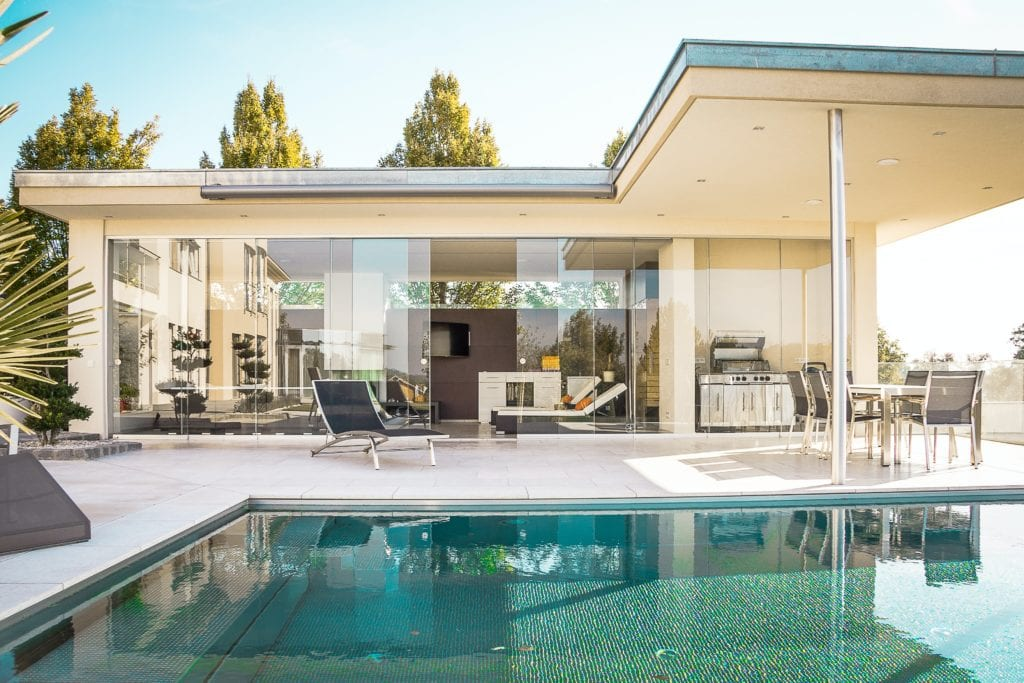 Off-white exterior of mid-century modern home with large siding glass doors, patio furniture and pool.