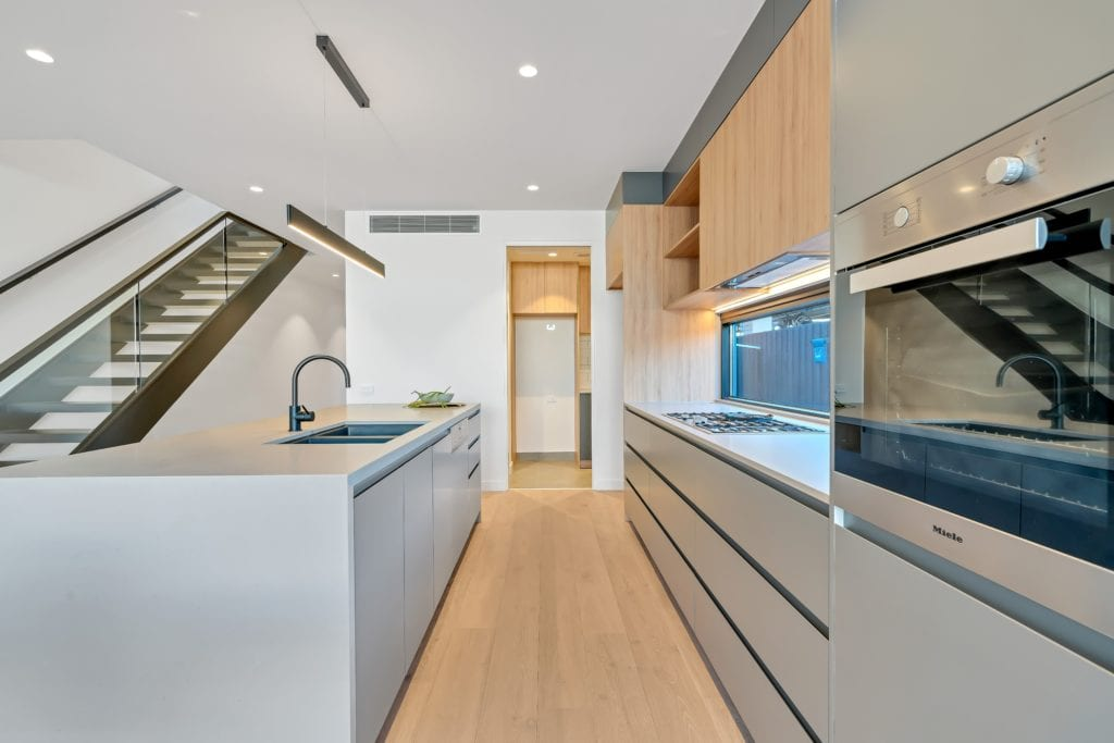 Modern minimalist kitchen with light grey cupboards, light wood upper cupboards, built-in oven and large island with sink.