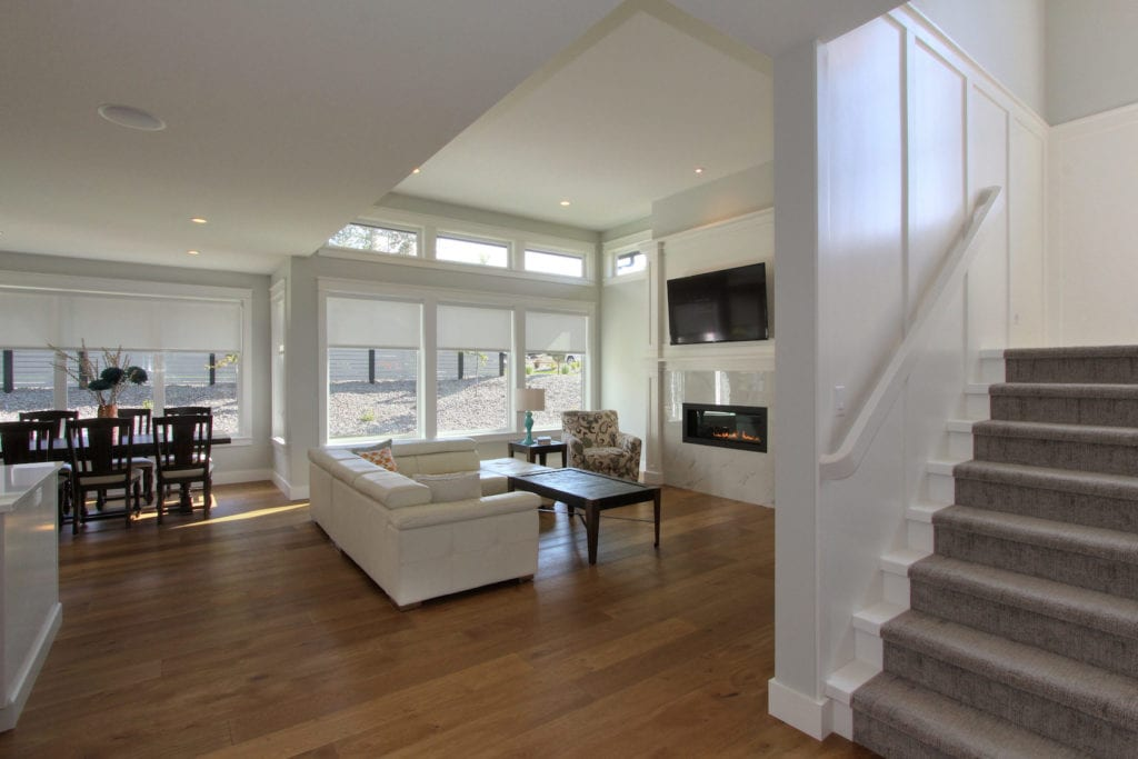 Interior image of living and dining area in a custom built home by Stark Homes with eco-friendly flooring, white walls, fireplace, and white sofa.