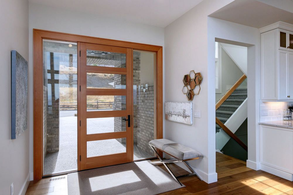 Stark Homes custom home view of the front door with sunlight shining in through glass panels relating to the sustainable building practices.
