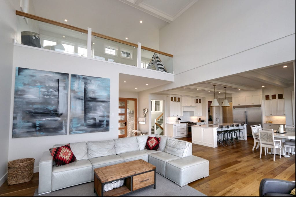 an open-concept living room and kitchen built by Stark Homes, integrating the custom home trend of natural wooden accents