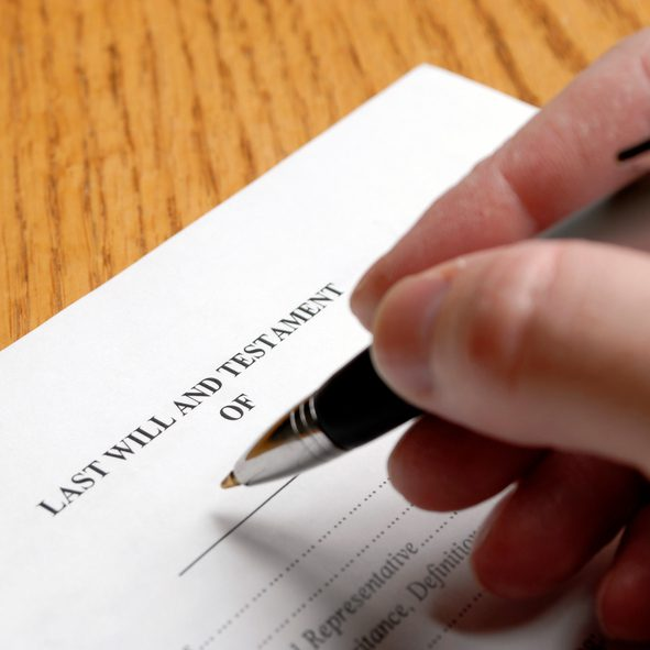 Person signing last will and testament with an elegant pen