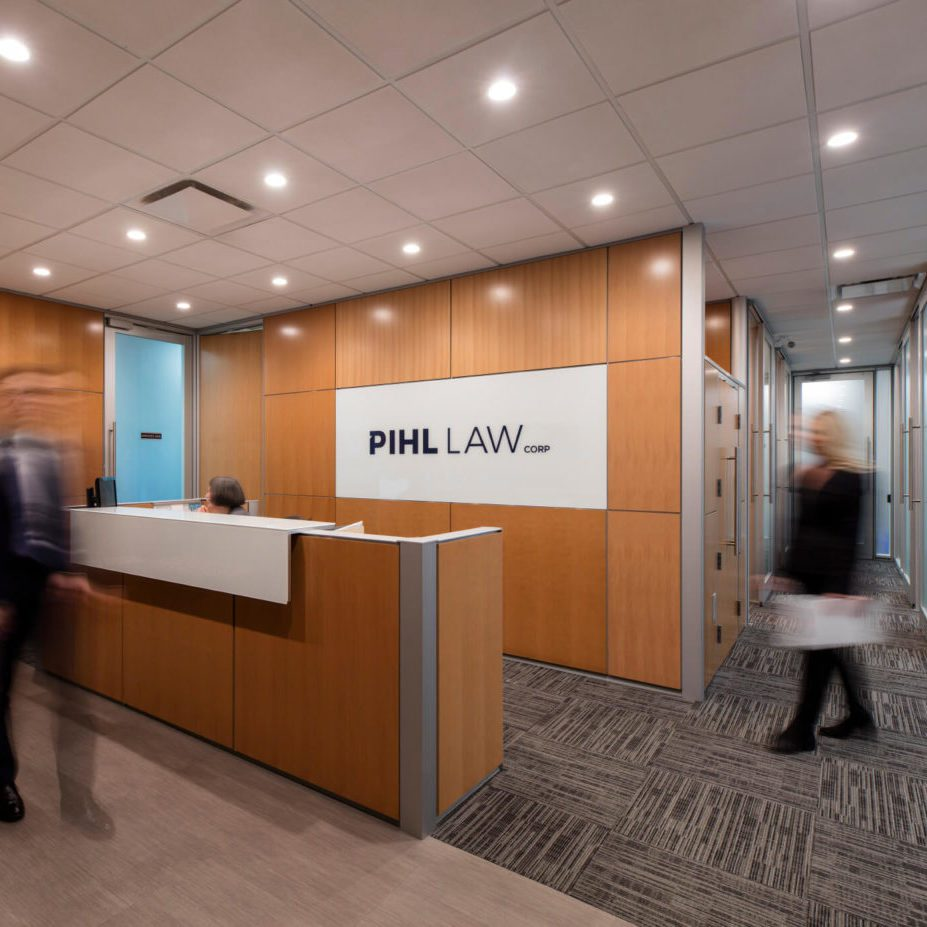 Pihl Law Office Reception with Employees Walking and Pihl Law logo on wooden background wall